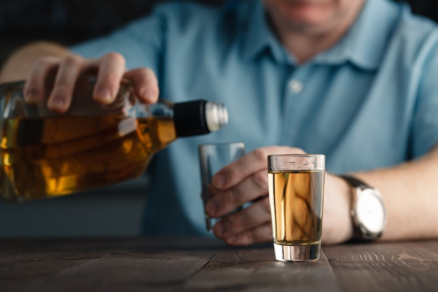 El hombre está vertiendo tequila en vaso