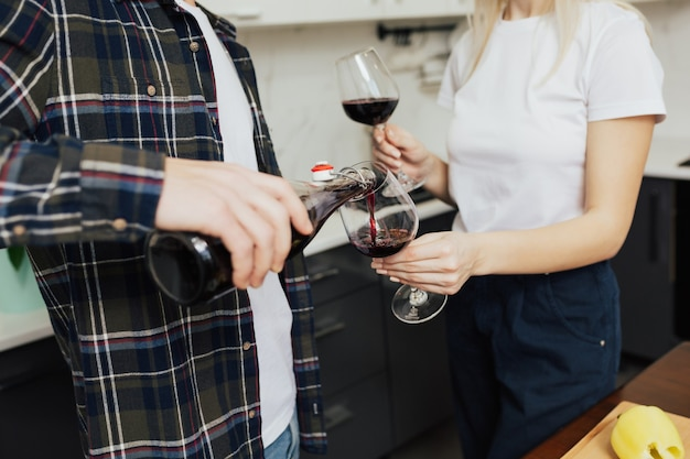 Hombre vertiendo vino tinto a la mujer en la cocina de casa