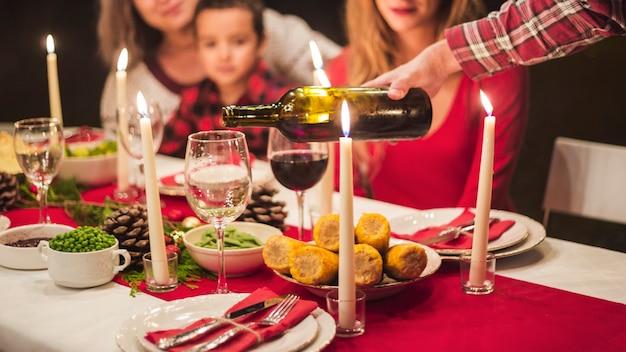 Hombre vertiendo winne en la cena de navidad