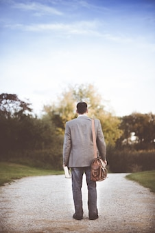 Hombre vestido con abrigo gris de pie cerca de la carretera durante el día