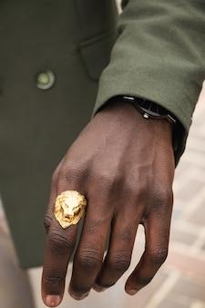 Hombre vestido con anillo de león dorado