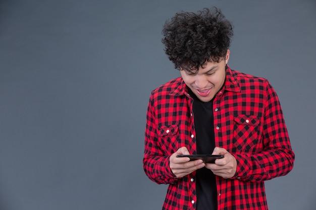 Un hombre vestido con una camisa a cuadros roja con un teléfono inteligente