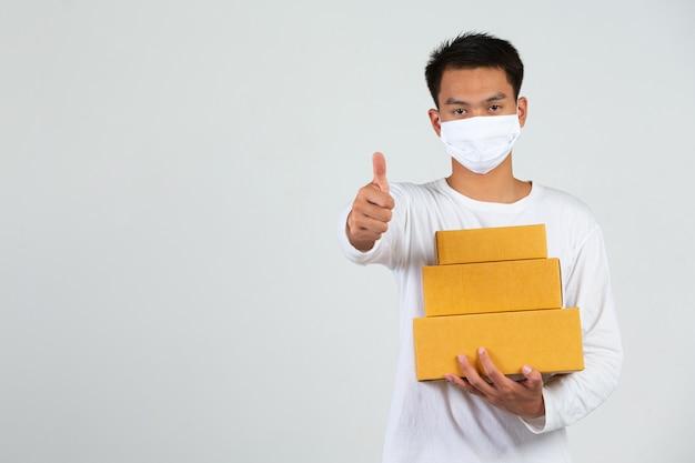 Un hombre vestido con una camiseta blanca sostiene un buzón marrón para entregar cosas. haga gestos y expresiones faciales.