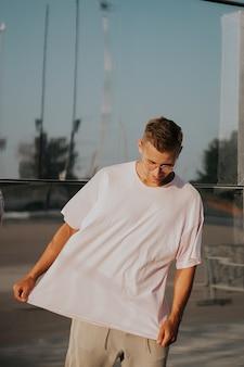 Hombre vestido con camiseta en blanco posando contra la pared del espejo de cristal en la calle de la ciudad, maqueta de camiseta frontal en modelo, estilo urbano