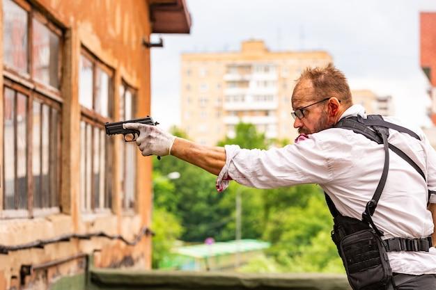Hombre vestido con un chaleco antibalas, una camisa en la sangre, persigue a una víctima con una pistola estilo de película de acción