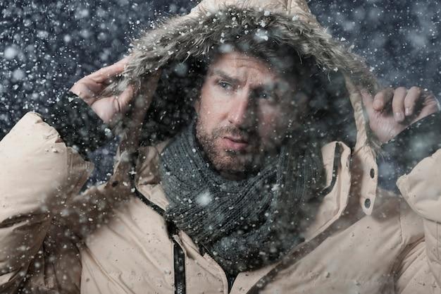 Hombre vestido con una chaqueta de invierno mientras está nevando