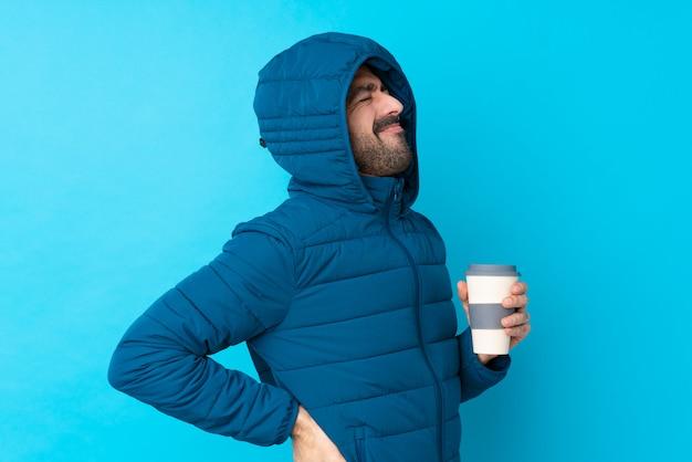 Hombre vestido con chaqueta de invierno y sosteniendo un café para llevar sobre una pared azul aislada que sufre de dolor de espalda por haber hecho un esfuerzo