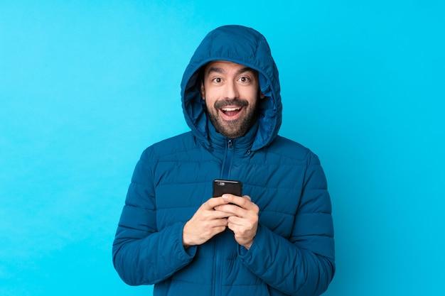 Hombre vestido con chaqueta de invierno y sosteniendo un café para llevar sobre pared azul aislado sorprendido y enviando un mensaje