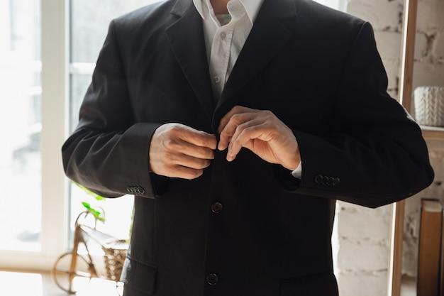 Hombre vestido con chaqueta negra. cerca de manos masculinas caucásicas. concepto de negocio, finanzas, trabajo, compras en línea o ventas.