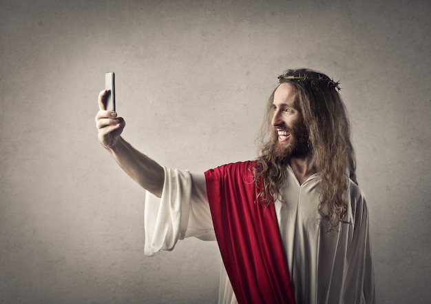 Hombre vestido como jesús tomando un selfie.