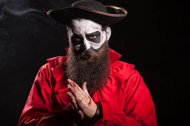 Hombre vestido como un pirata aterrador para la celebración de halloween sobre fondo negro.
