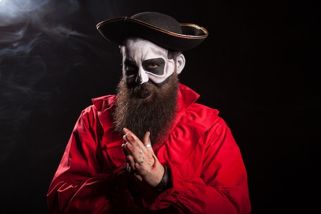 Hombre vestido como un pirata medieval espeluznante sobre fondo negro para halloween.