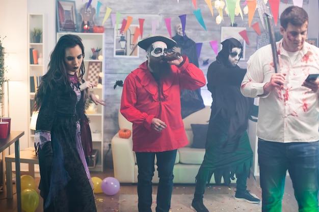 Hombre vestido como un zombi con un hacha usando un teléfono inteligente en la fiesta de halloween.