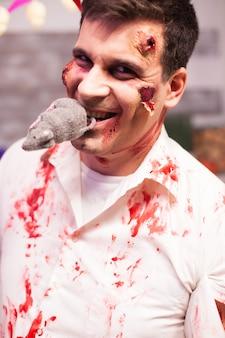 Hombre vestido como un zombi sangriento con una rata en la boca en la celebración de halloween.