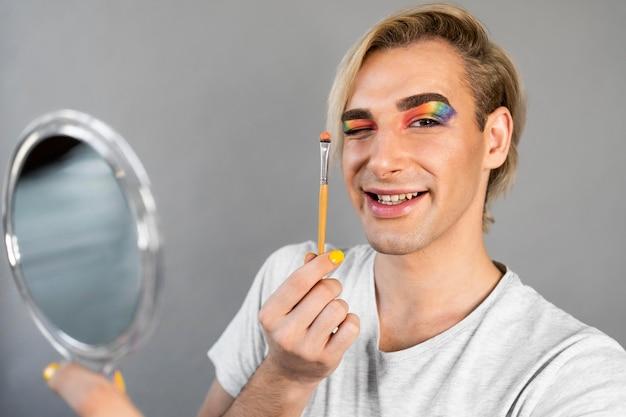 Hombre vestido con cosméticos de maquillaje y pincel de sujeción