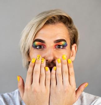 Hombre vestido con cosméticos de maquillaje y primer plano de esmalte de uñas