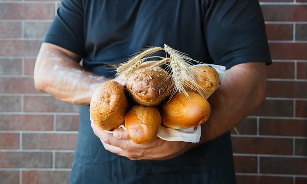 Hombre vestido con delantal con pan recién horneado