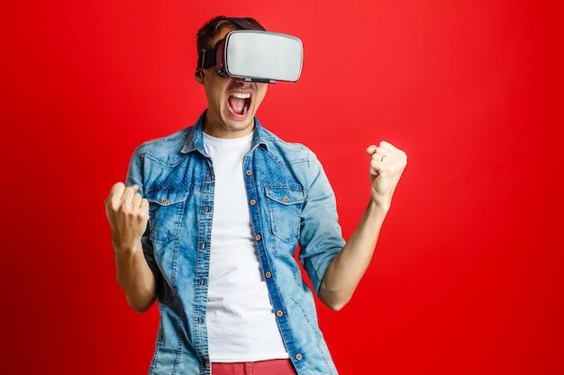 Hombre vestido con gafas de realidad virtual sobre fondo rojo.