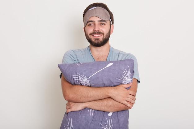 Hombre vestido gris casual camiseta lista para ir a la cama, con la pared blanca. chico con cara feliz tiene almohada. macho con barba y bigote relajándose, durmiendo la siesta, descansando en casa
