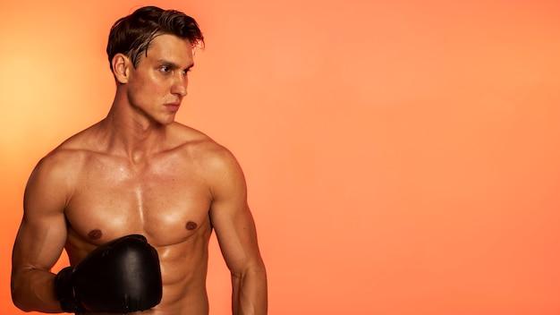 Hombre vestido con guantes de boxeo con espacio de copia