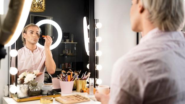 Hombre vestido con maquillaje cantar un pincel en su rostro