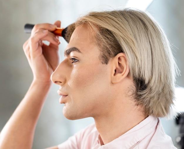 Hombre vestido con maquillaje con cepillo