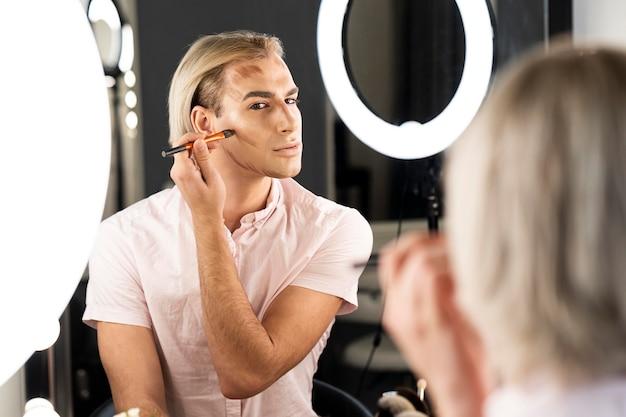 Hombre vestido con maquillaje haciendo su contorno de rostro