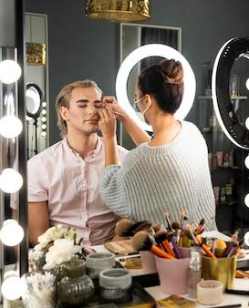 Hombre vestido con maquillaje y mujer ayudándolo