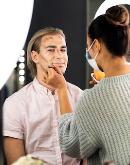Hombre vestido con maquillaje y mujer haciendo su contorno