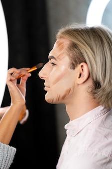 Hombre vestido con maquillaje y persona haciendo su vista lateral de contorno