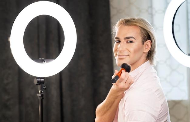 Hombre vestido con maquillaje sentado junto al espejo de luz