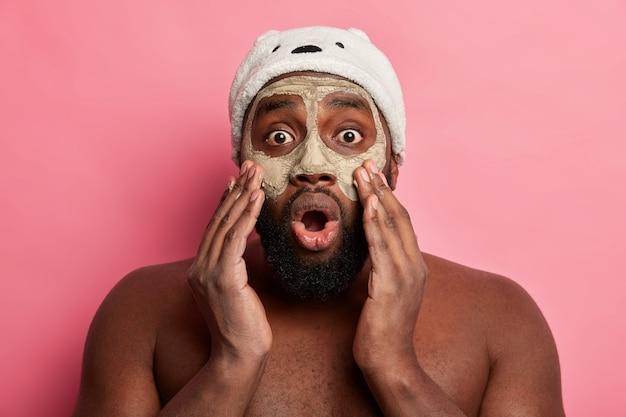 Hombre vestido con máscara cosmética en la cara para el cuidado de la piel dermatología