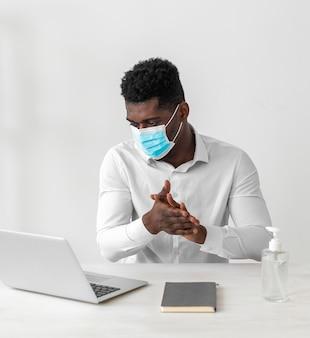 Hombre vestido con máscara y limpiándose las manos