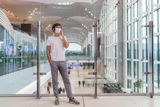 Hombre vestido con mascarilla en el aeropuerto y hablando por teléfono inteligente