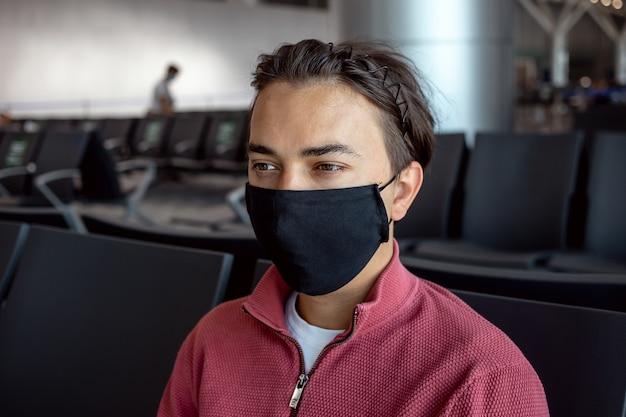 Hombre vestido con mascarilla en el aeropuerto. los temas viajan en nueva normalidad, coronavirus y protección personal.