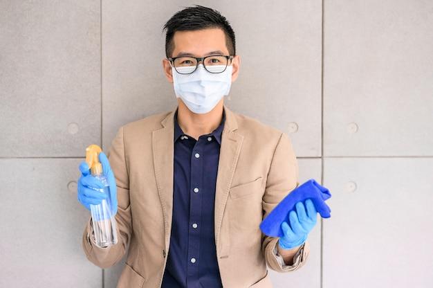 Hombre vestido con mascarilla y guantes con alcohol en spray y paño de microfibra