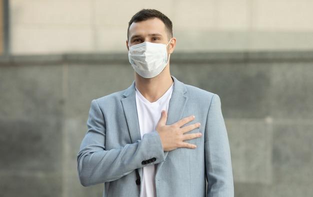 Hombre vestido con mascarilla quirúrgica saluda con su mano sobre el corazón