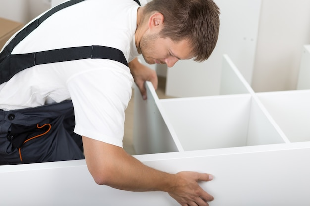 Hombre vestido con muebles de montaje general de trabajadores sentados en el suelo en casa nueva. bricolaje, hogar y concepto de mudanza