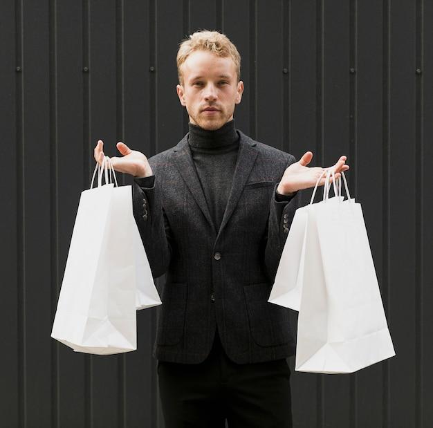 Hombre vestido de negro con bolsas de compras