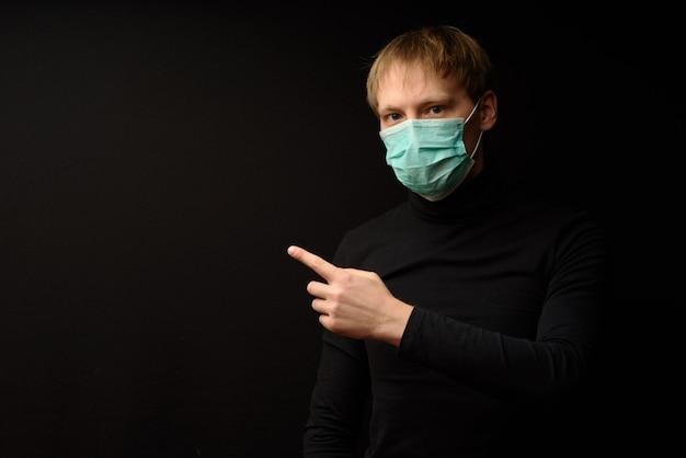 Un hombre vestido de negro sobre negro con una máscara protectora está vendiendo su producto.