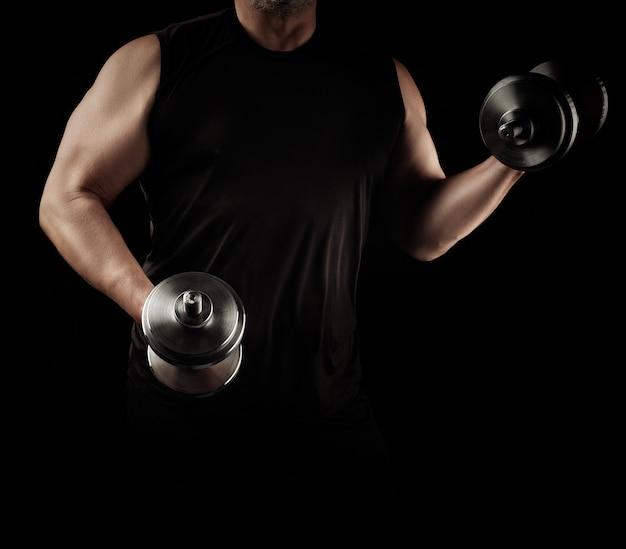 El hombre vestido de negro tiene pesas de acero en sus manos, sus músculos están tensos
