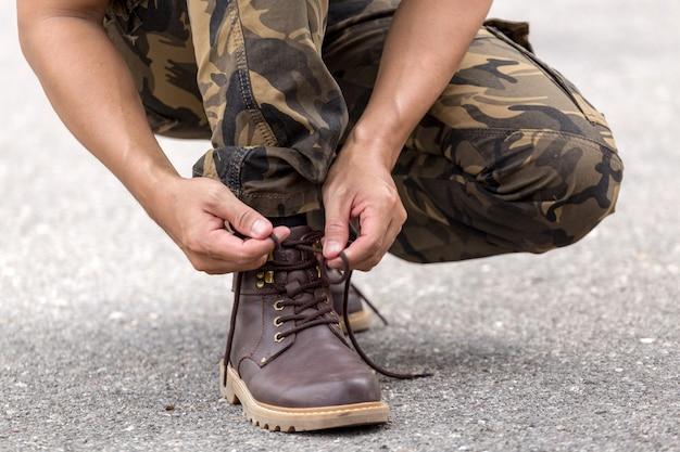 Hombre vestido con pantalones de carga y atar los cordones en los zapatos de cuero de arranque