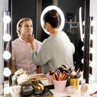 Hombre vestido con pinceles de maquillaje y maquillaje