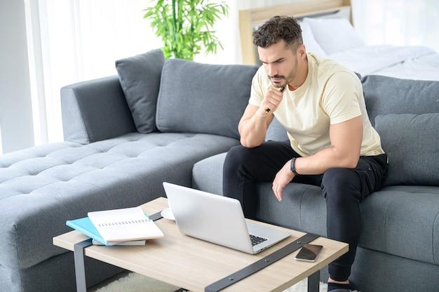 Un hombre vestido con ropa informal trabajando desde casa, reuniones en línea, videollamadas, conferencias y estudios en línea con estrés