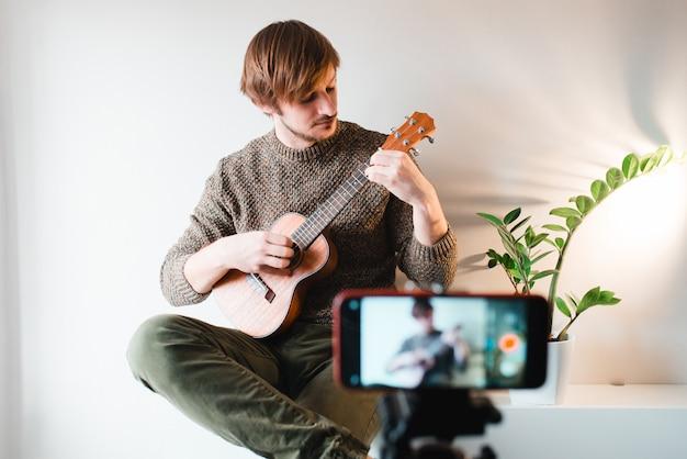 Hombre vestido con un suéter saca el vlog de un juego en un ukelele en casa por teléfono.