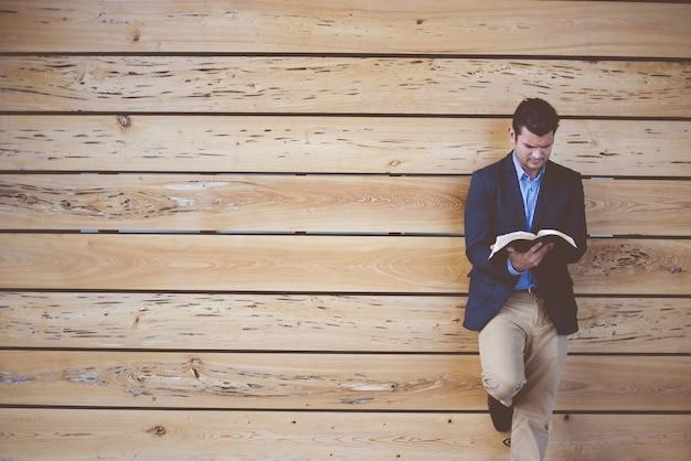Hombre vestido con un traje apoyado contra la pared mientras lee la biblia