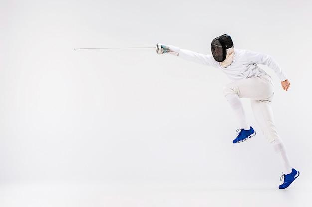 Hombre vestido con traje de esgrima practicando con espada contra gris