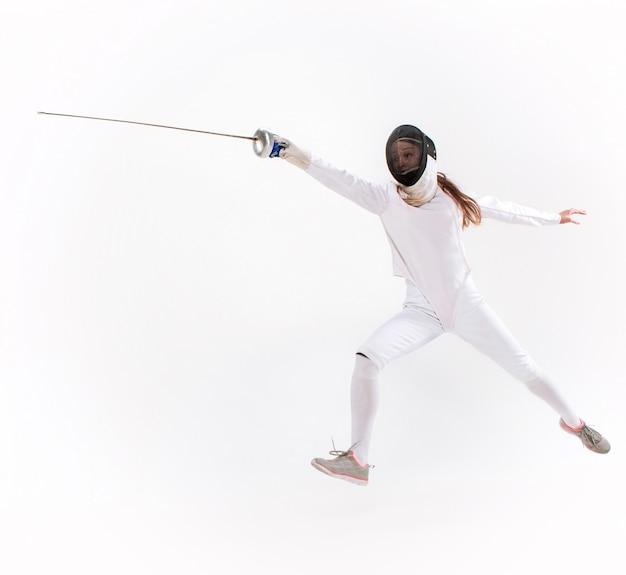 Hombre vestido con traje de esgrima practicando con espada