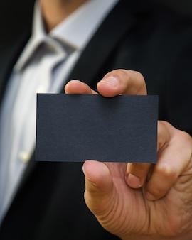 Hombre vestido con un traje y sosteniendo una tarjeta de visita negra.