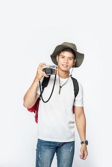 Un hombre vestido para viajar con sombrero y tomando una cámara.